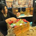 Perla Catalan digs through a chest of fake treasure as she helps set up a booth for the 2014 pirate ...
