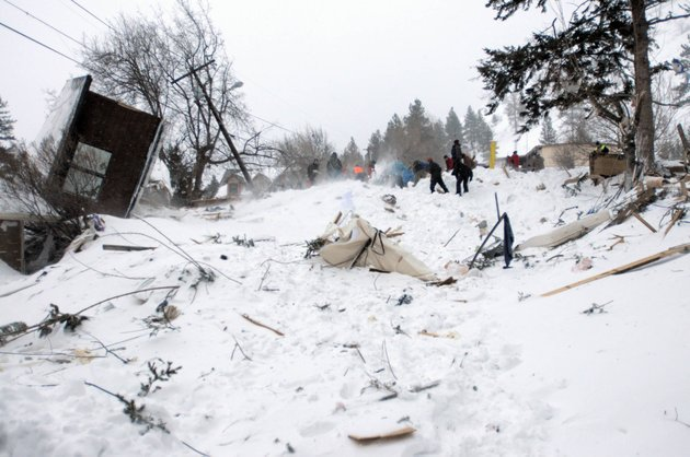 rescuers-dig-at-the-scene-of-an-avalanche-in-missoulas-rattlesnake-valley-on-friday-feb-28-2014-the-avalanche-roared-into-a-residential-neighborhood-and-destroyed-a-house-but-three-people-were-found-alive-amid-the-snow-and-wreckage-police-said-the-survivors-were-an-elderly-couple-and-an-8-year-old-boy-police-sgt-travis-welsh-said