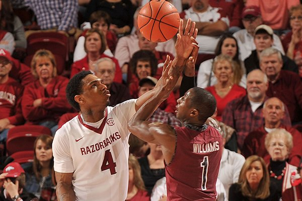 Arkansas forward Coty Clarke knocks the ball out of the hands of South Carolina defender Brenton Williams during the second half of a Wednesday, Feb. 19, 2014 game at Bud Walton Arena in Fayetteville.