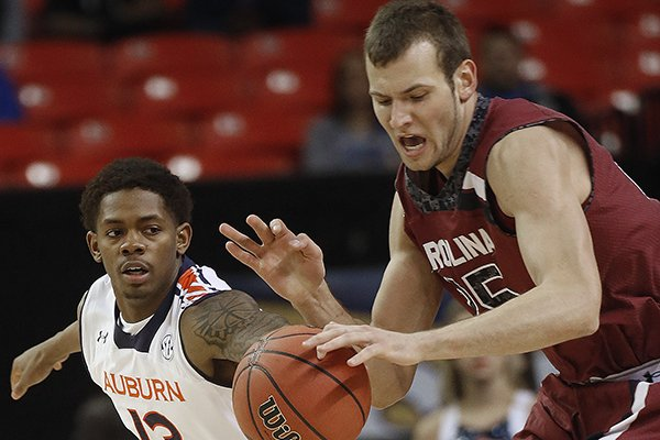 South Carolina forward Mindaugas Kacinas (25) and Auburn guard Tahj Shamsid-Deen (13) vie for a loose ball during the first half in a first round Southeastern Conference tournament game, Wednesday, March 12, 2014, in Atlanta. (AP Photo/John Bazemore)