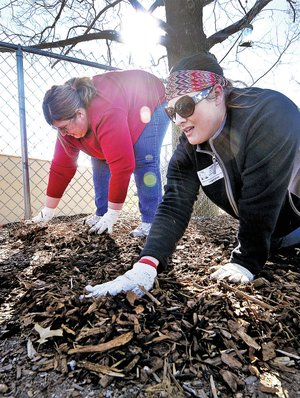 STAFF PHOTO BEN GOFF Pope, right, and Tracy Price spread mulch at the Helen R. Walton Children's Enrichment Center in Bentonville.