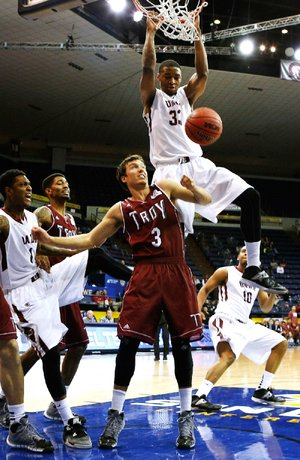 Special to the Arkansas Democrat Gazette/JONATHAN BACHMAN - 03/13/2014 -  UALR forward James White (33) dunks the ball over Troy guard Jeff Mullahey (3) during second half action in the quarterfinal round of the Sunbelt Tournament in New Orleans, March 12, 2014. UALR won 74-61.
