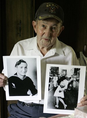 FILE - In this July 31, 2007 file photo, Glenn McDuffie holds a portrait of himself as a young man, left, and a copy of Alfred Eisenstaedt's iconic Life magazine shot of a sailor, who McDuffie claims is him, embracing a nurse in a white uniform in New York's Times Square, at his Houston home. McDuffie, who became known for claiming he was the sailor kissing a woman in Times Square in a famous World War II-era photo taken by a Life magazine photographer has died. Houston Police Department forensic artist Lois Gibson, who says she identified McDuffie as the man in the picture, says Friday, March 14, 2014 that he died March 9. McDuffie was 86.
