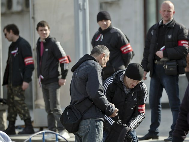 members-of-the-crimean-self-defense-forces-check-a-passenger-at-the-main-railway-station-in-simferopol-ukraine-friday-march-14-2014-members-of-the-crimean-self-defense-forces-check-the-luggage-and-identity-documents-of-passengers-arriving-by-train-especially-from-western-ukrainian-cities-or-the-capital-to-simferopol-looking-for-what-they-label-as-provocateurs-ahead-of-the-march-16-referendum-that-will-ask-residents-if-they-want-the-territory-to-become-part-of-russia