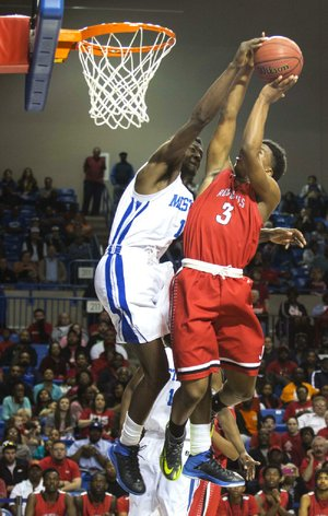 Forrest City's Trent Stein (left) goes high to block a shot by Jacksonville's Devin Campbell on Friday in the Class 5A boys championship game in Hot Springs. Stein, who had four points and five rebounds, and the Mustangs defeated the Red Devils 69-60. High school, Pages 4-5C.