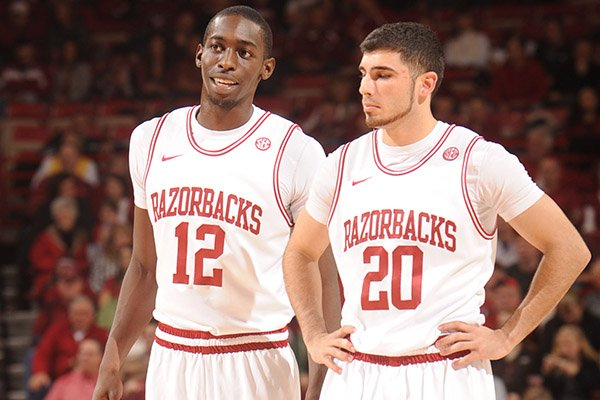 Arkansas guards and former Fayetteville High School standouts Fred Gulley (12) and Kikko Haydar speak Saturday, Jan. 5, 2013, during the second half of play against Delaware State in Bud Walton Arena in Fayetteville.