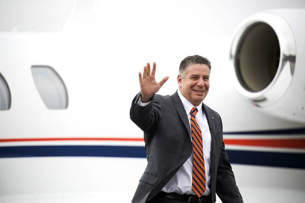 Auburn's new basketball coach Bruce Pearl, former coach of Tennessee, waives to fans after exiting the plane at the Auburn Regional Airport in Auburn, Ala., on Tuesday, March 18, 2014. Auburn announced the hiring on Tuesday of the NCAA college basketball coach. (AP Photo/Opelika-Auburn News, Albert Cesare)