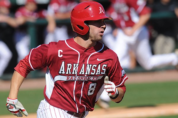 Arkansas center fielder Tyler Spoon heads to first as a run scores against Grambling State during the third inning Wednesday, March 19, 2014, at Baum Stadium in Fayetteville.