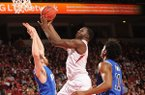 Arkansas forward Alandise Harris , center, reaches to score past Indiana State forward Justin Gant, left, during the second half Tuesday, March 18, 2014, at Bud Walton Arena in Fayetteville.