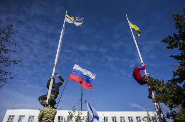 members-of-the-crimean-pro-russian-self-defense-forces-climb-up-to-take-down-a-ukrainian-flag-right-and-a-ukrainian-navy-flag-left-at-the-ukrainian-navy-headquarters-in-sevastopol-crimea-on-wednesday-march-19-2014-crimeas-self-defense-forces-on-wednesday-stormed-the-ukrainian-navy-headquarters-in-the-black-sea-port-of-sevastopol-taking-possession-without-resistance-a-day-after-russia-signed-a-treaty-with-local-authorities-to-annex-the-region-in-center-is-a-russian-flag
