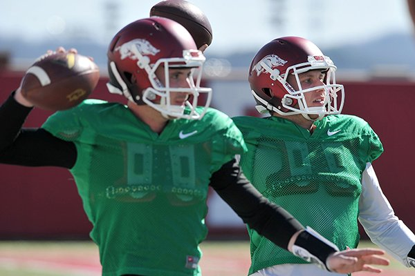 Arkansas quarterbacks Brandon Allen (left) and Austin Allen run drills during practice Thursday afternoon in Fayetteville.