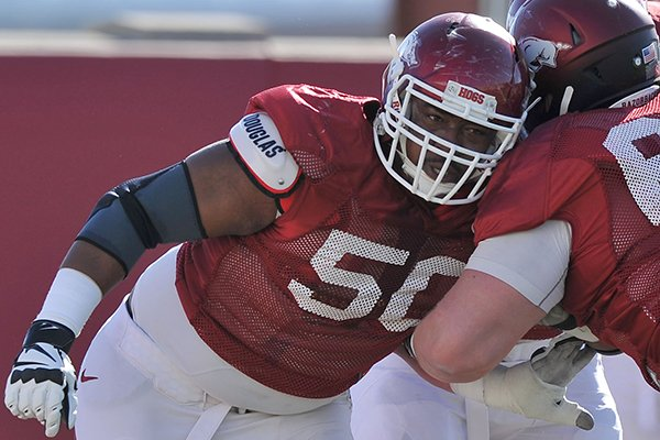 Arkansas offensive lineman Grady Ollison runs drills during practice Thursday, March 20, 2014 in Fayetteville.
