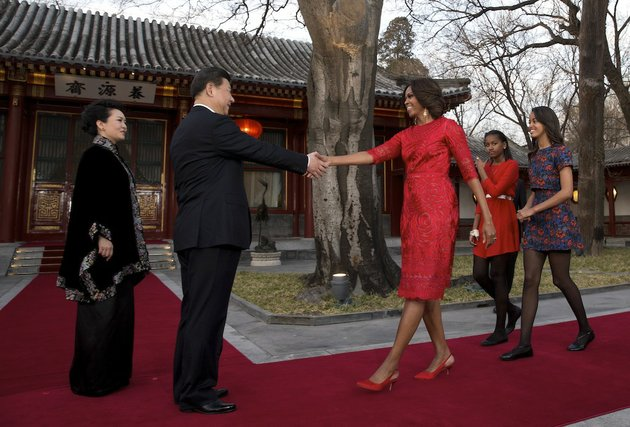 us-first-lady-michelle-obama-third-from-right-her-daughters-malia-right-and-sasha-second-from-right-is-greeted-by-chinese-president-xi-jinping-second-from-left-and-his-wife-peng-liyuan-left-at-the-diaoyutai-state-guest-house-in-beijing-china-friday-march-21-2014-us-first-lady-michelle-obama-met-with-excited-students-who-were-building-robots-and-tried-her-hand-at-chinese-calligraphy-friday-during-a-tour-of-a-beijing-high-school