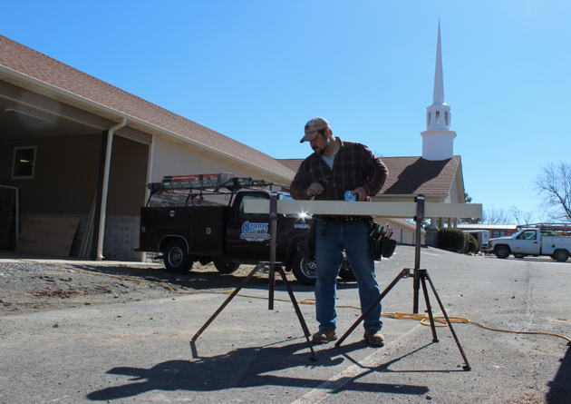 tom-hendrix-a-carpenter-with-ozark-construction-measures-a-gutter-as-he-works-on-the-finishing-touches-of-rebuilding-the-botkinburg-foursquare-church-on-a-recent-afternoon