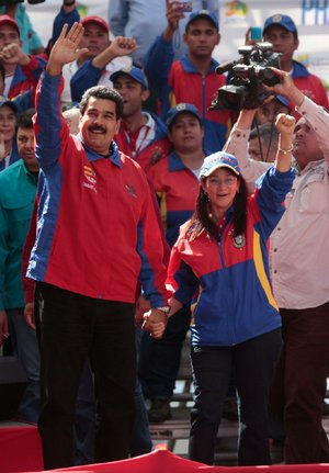 Venezuela's President Nicolas Maduro and his wife Cilia Flores greet supporters upon their arrival for a meeting with students in Caracas, Venezuela, Saturday, March 22, 2014. Two more people were reported dead in Venezuela as a result of anti-government protests even as supporters and opponents of Maduro took to the streets on Saturday in new shows of force. (AP Photo/Esteban Felix)