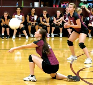 File Photo by Randy Moll Jordan Olds drops to a knee to set up a serve during play in Gentry last fall. Haley Borgeteien-James stands ready behind her.