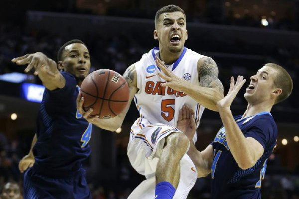 Florida guard Scottie Wilbekin (5) flies by UCLA guard Norman Powell (4) and UCLA forward Travis Wear, right, during the first half in a regional semifinal game at the NCAA college basketball tournament, Thursday, March 27, 2014, in Memphis, Tenn. (AP Photo/Mark Humphrey)