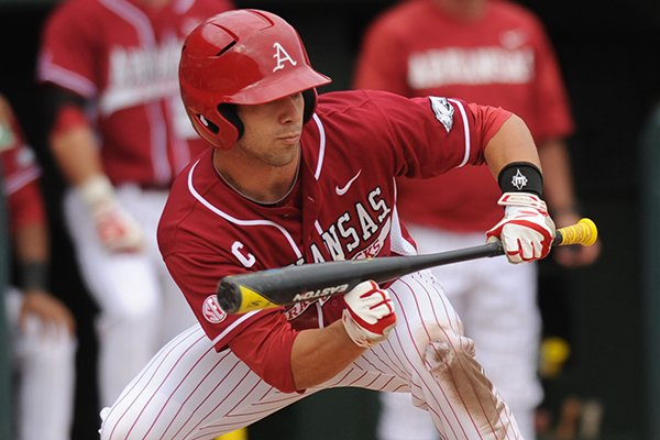 Arkansas' Tyler Spoon lays down a bunt to move Brian Anderson into scoring position during the eighth inning of play against Alabama Saturday, March 22, 2014, at Baum Stadium in Fayetteville.
