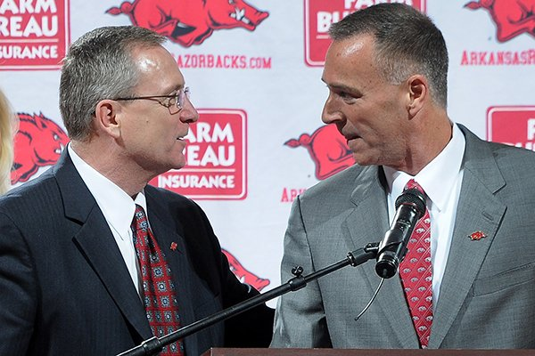 Jeff Long, director of athletics and vice chancellor, left, congratulates Jimmy Dykes after being introduced as the eighth women's head basketball coach Sunday, March 30, 2014, at Bud Walton Arena in Fayetteville.