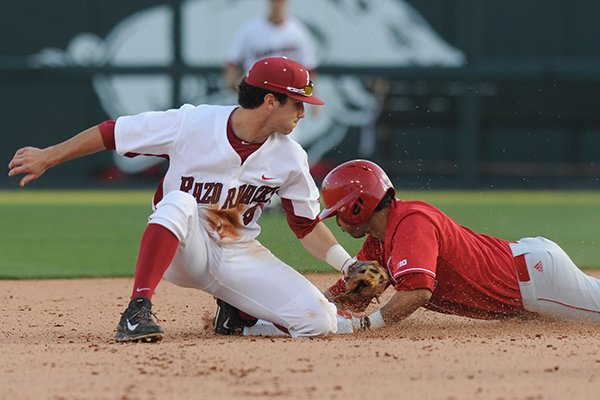 Arkansas shortstop Brett McAfee reaches to apply the late tag to Nebraska shortstop Steven Reveles as Reveles slides in safely at second during the second inning Tuesday, April 1, 2014, at Baum Stadium in Fayetteville.