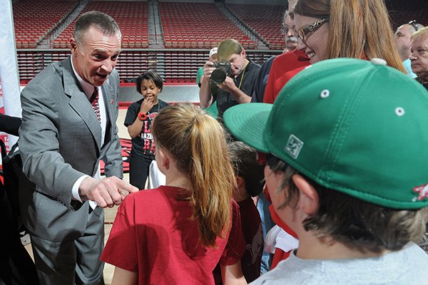 Jimmy Dykes, left, speaks to Grace Kilcrease, 9, after a press conference introducing him as the eighth women's head basketball coach Sunday, March 30, 2014, at Bud Walton Arena in Fayetteville.