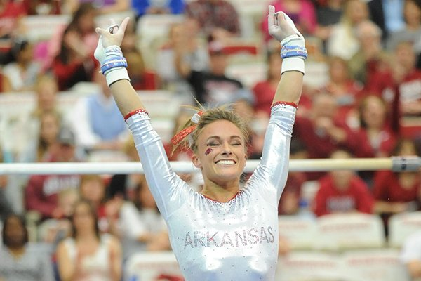 Arkansas' Katherine Grable celebrates after competing in the bars during a meet with Kentucky Friday, Feb. 21, 2014, at Barnhill Arena in Fayetteville.