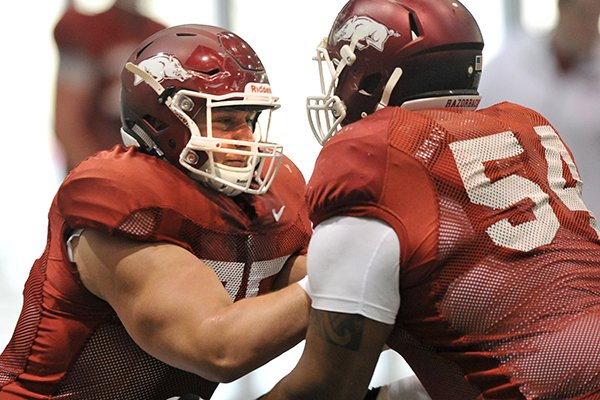 Arkansas center Luke Charpentier runs drills during Thursday afternoon's practice in Fayetteville.