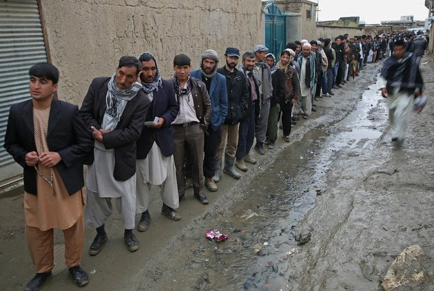afghan-men-line-up-for-registration-process-before-they-cast-their-votes-at-a-polling-station-in-kabul-afghanistan-saturday-april-5-2014-afghans-flocked-to-polling-stations-nationwide-on-saturday-defying-a-threat-of-violence-by-the-taliban-to-cast-ballots-in-what-promises-to-be-the-nations-first-democratic-transfer-of-power