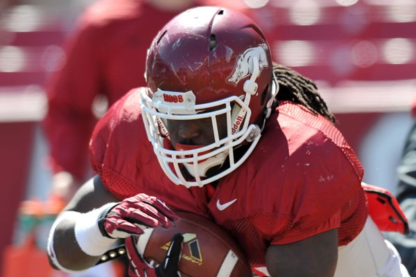 Arkansas running back Alex Collins runs drills during practice Saturday, April 5, 2014, at Razorback Stadium in Fayetteville.