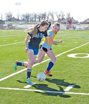 Special To NWA Media Skot Lindstedt Evie Cannon, left, Springdale Har-Ber soccer player practices with a teammate on Friday.