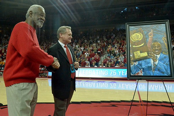 Former University of Arkansas basketball coach Nolan Richardson shakes the hand of David Gearhart, University of Arkansas Chancellor, during a presentation of a painting of Richareson on Saturday, Feb. 2, 2013 at Bud Walton Arena in Fayetteville.