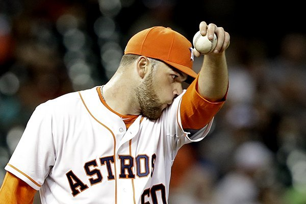 Houston Astros starting pitcher Dallas Keuchel wipes his face after giving up a single to Los Angeles Angels' Josh Hamilton in the third inning of a baseball game on Saturday, April 5, 2014, in Houston. (AP Photo/Pat Sullivan)