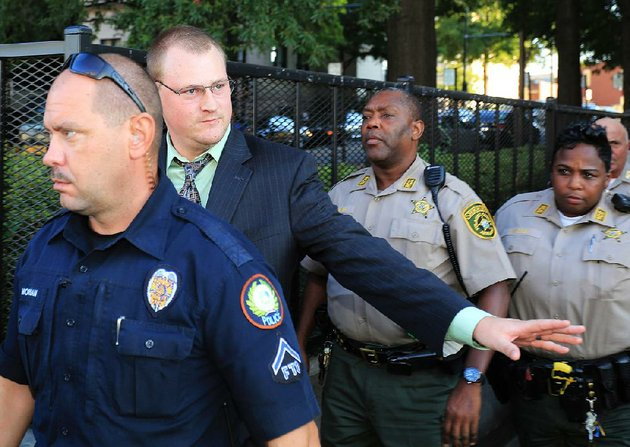 file-former-little-rock-police-officer-josh-hastings-waves-to-some-little-rock-police-officers-as-he-is-escorted-out-of-the-pulaski-county-courthouse-after-his-manslaughter-trial-ended-in-a-2nd-mistrial-on-sept-24-2013-in-little-rock
