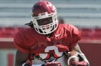 Arkansas running back Alex Collins runs drills during practice Saturday morning at Razorback Stadium in Fayetteville.