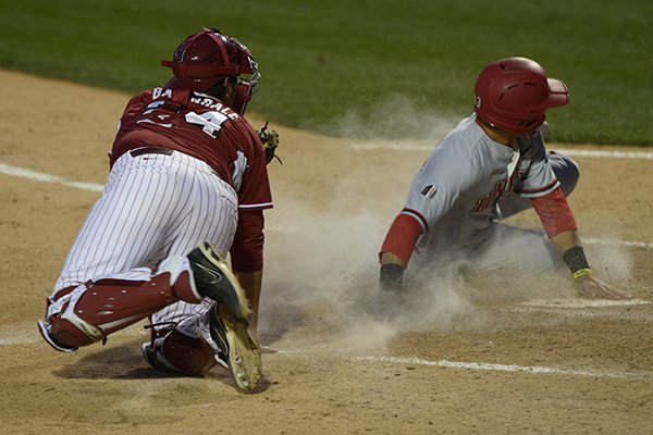 Arkansas catcher Blake Baxendale (24) tries to apply the tag to UNLV's Joey Armstrong at the plate Tuesday, April 8, 2014 at Baum Stadium in Fayetteville. Armstrong was safe on the play.