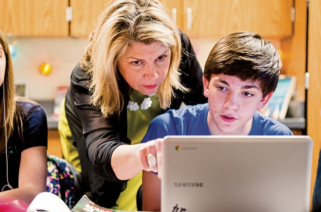 deana-davis-an-english-teacher-at-cabot-junior-high-school-north-helps-eighth-grader-ryan-travis-with-a-project-on-one-of-the-chromebooks-the-district-has-purchased