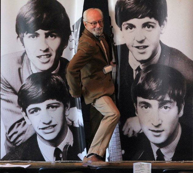 jeff-baskin-executive-director-of-the-william-f-laman-public-library-system-in-north-little-rock-climbs-through-a-banner-of-the-beatles-during-an-earlier-news-conference-announcing-the-british-invasion-50-years-later-a-photographic-exhibit-on-fab-four-opening-saturday-and-continuing-daily-monday-april-19-at-several-businesses-and-public-locales-in-and-around-the-downtown-argenta-historic-district