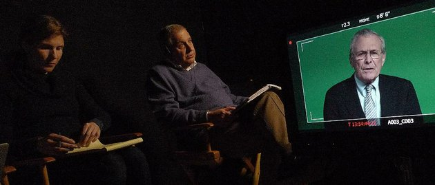 a-production-assistant-left-takes-notes-as-director-errol-morris-interviews-former-secretary-of-defense-donald-rumsfeld-shown-on-screen-for-his-documentary-the-unknown-known