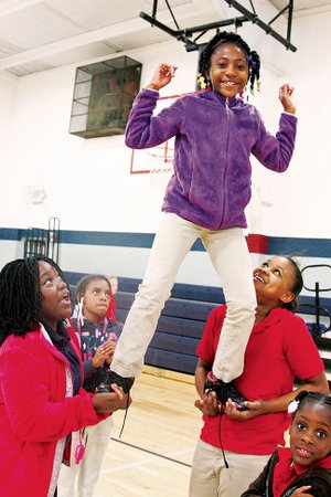 Travisha Garner is hoisted up by Jayla Taylor, left, and Brooke Compton in the gym at the Jacksonville Boys and Girls Club. Some of the proceeds from Homecoming of a Champion Week will go toward operations and maintenance of the club.