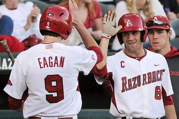 Arkansas' Clark Eagan, left, and Tyler Spoon high-five after scoring runs off of a bunt by Jake Wise during the game against UNLV in Baum Stadium in Fayetteville on Wednesday April 9, 2014. Arkansas won 9-2.