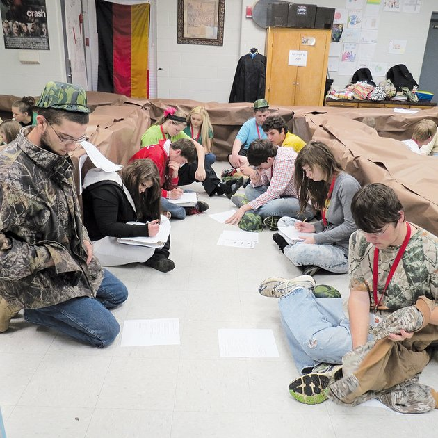 from-left-nick-middleton-crystal-mitchell-garrett-sherrill-sydney-wader-alli-shock-dylan-duncan-paris-carpenter-adam-barnard-lindsey-bates-and-kolten-reinier-sit-on-the-floor-in-candace-churchwells-classroom-simulating-the-trenches-of-world-war-i
