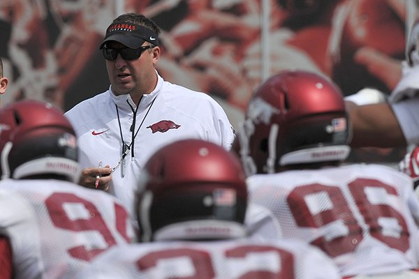 Arkansas coach Bret Bielema works with his team before the start of Saturday's football scrimmage at Razorback Stadium in Fayetteville.