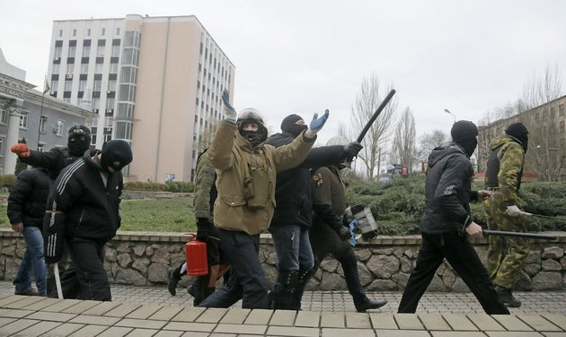 masked-pro-russian-activists-march-after-leaving-a-regional-prosecutors-office-in-donetsk-ukraine-saturday-april-12-2014-saturday-morning-a-group-of-pro-russian-activists-armed-with-metal-sticks-seized-the-office-later-they-left-the-building-after-talks-with-police-nobody-was-arrested