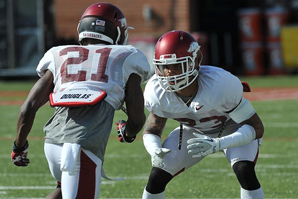 Arkansas cornerbacks Tevin Mitchel (23) and Carroll Washington (21) run drills during practice Thursday, April 10, 2014 in Fayetteville.