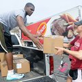 Shelby Harper, volleyball athlete, right, hands a box to Manuale Watkins, basketball athlete, while ...
