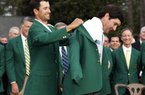 Defending Masters' champion Adam Scott, of Australia, helps Bubba Watson, right, with his green jacket after winning the Masters golf tournament Sunday, April 13, 2014, in Augusta, Ga. (AP Photo/Darron Cummings)