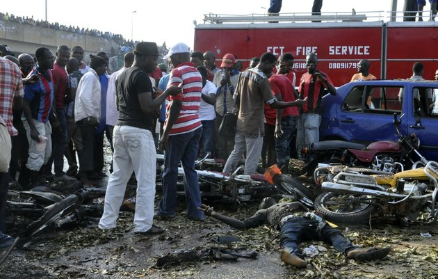 people-gather-at-the-site-of-a-blast-at-the-nyanya-motor-park-about-16-kilometers-10-miles-from-the-center-of-abuja-nigeria-on-monday-april-14-2014-an-explosion-blasted-through-a-busy-commuter-bus-station-on-the-outskirts-of-abuja-early-monday-as-hundreds-of-people-were-traveling-to-work