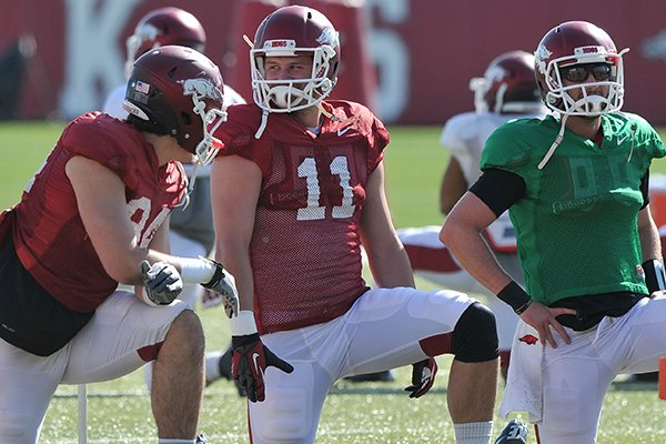 Arkansas tight end A.J. Derby (center) stretches with teammates during the Razorbacks practice Thursday afternoon in Fayetteville.