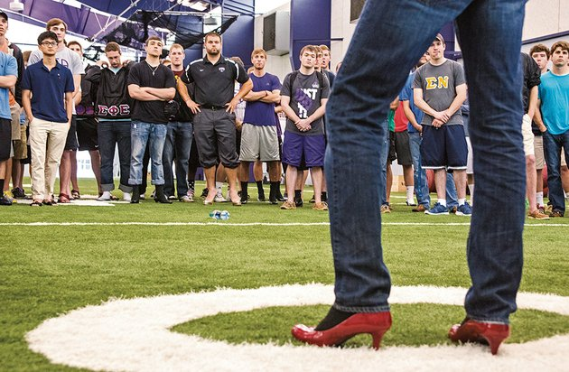 while-sporting-a-pair-of-red-high-heels-randy-young-president-of-the-university-of-central-arkansas-interfraternity-council-speaks-to-the-crowd-of-participants-in-the-walk-a-mile-in-her-shoes-event-at-uca-the-mens-march-part-of-a-national-event-is-designed-to-stop-rape-sexual-assault-and-gender-violence-against-women-the-uca-walk-was-organized-by-the-interfraternity-council-the-uca-police-department-the-division-of-university-and-government-relations-and-help-for-abuse-victims-in-emergency-need-in-conway