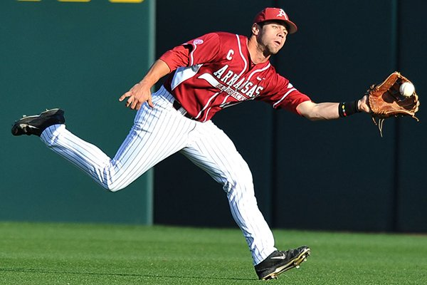 Arkansas center fielder Tyler Spoon runs down a fly ball for an out in the first inning of a game Saturday, April 5, 2014 against South Carolina at Baum Stadium in Fayetteville.
